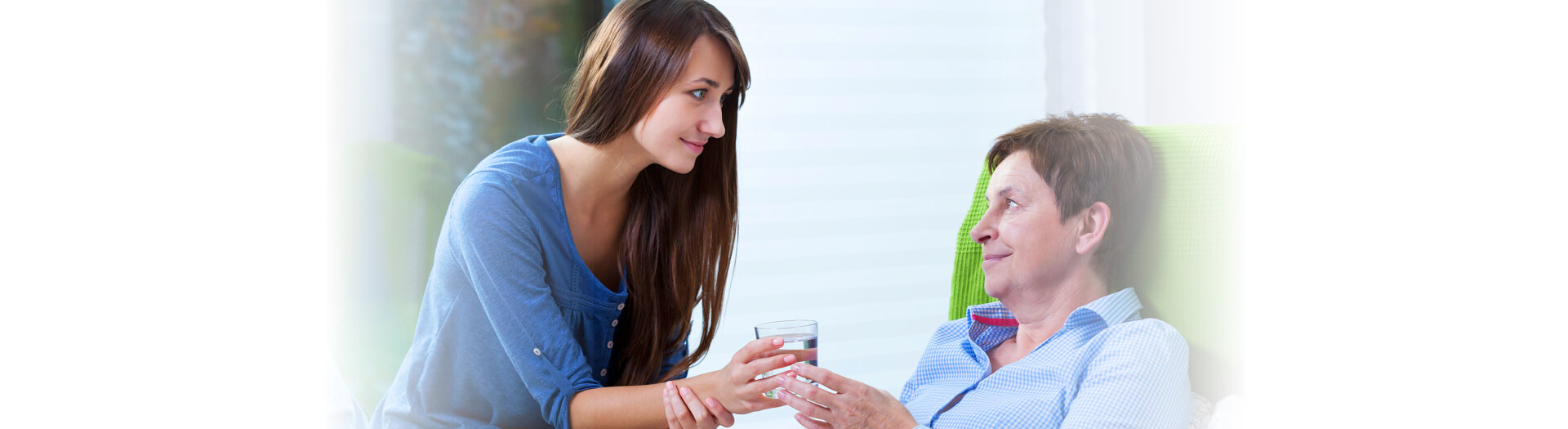 Caregiver giving glass of water to a senior
